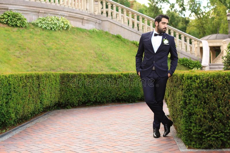 Stilig ung brudgum i elegant dräkt utomhus arkivfoto