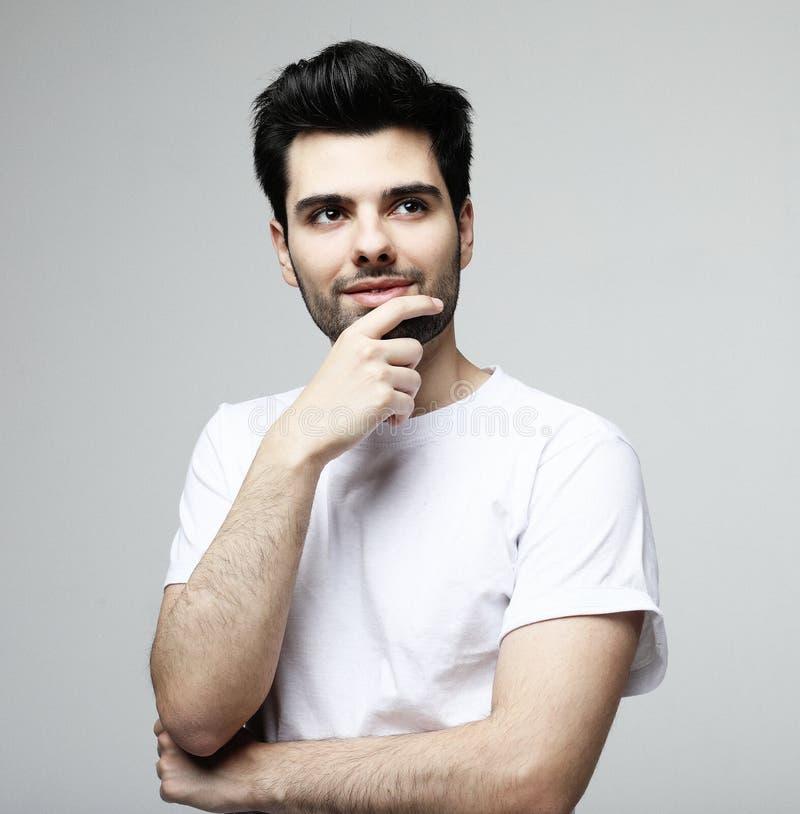 Stilig ung brunettman i smarta tillfälliga kläder som ser kameran, över vit bakgrund arkivfoton