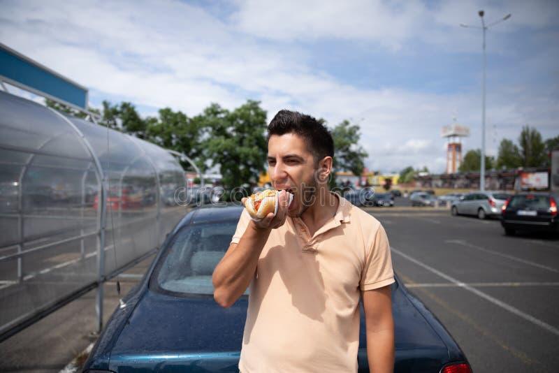 Stilig ung brunettman som äter varmkorven fotografering för bildbyråer