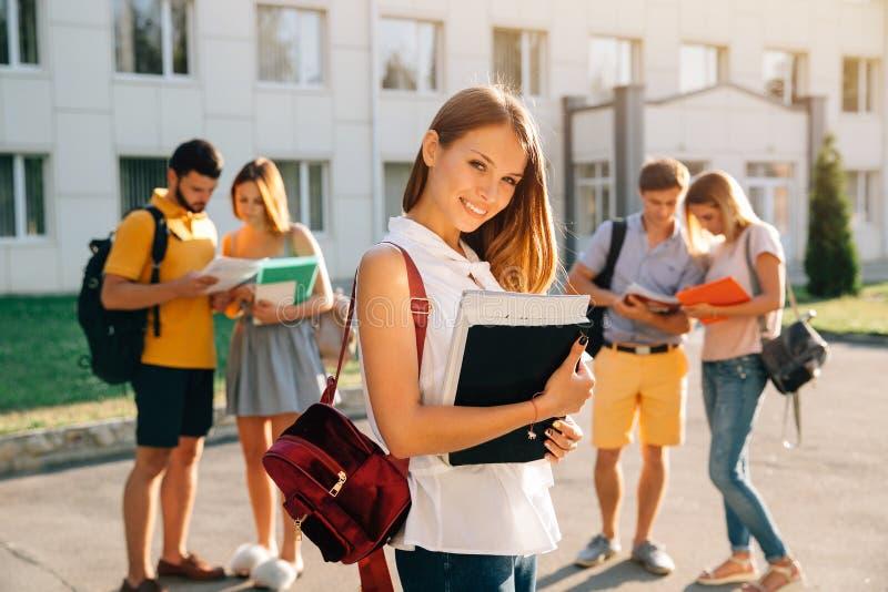 Stilig ung flicka med den röda sammetryggsäcken som rymmer böcker och ler, medan stå mot universitet med hennes vänner i fotografering för bildbyråer