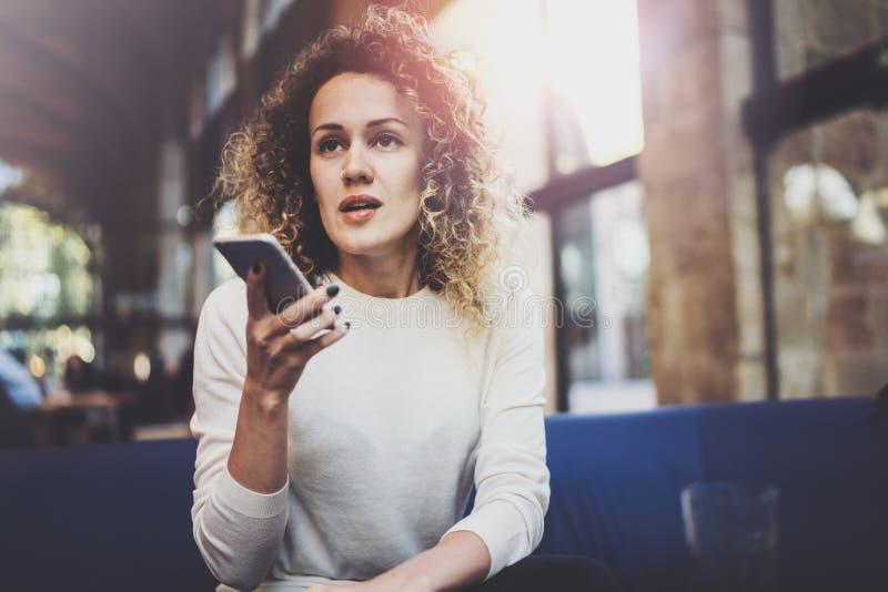 Stilig ung flicka som bär tillfällig kläder och använder mobiltelefonen under hennes vilotid i coffee shop Bokeh och signalljus fotografering för bildbyråer