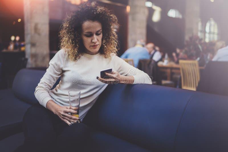 Stilig ung flicka som bär tillfällig kläder och använder mobiltelefonen under hennes vilotid i coffee shop Bokeh och signalljus royaltyfri bild