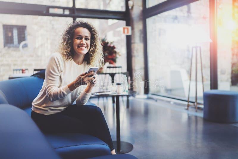 Stilig ung flicka som bär tillfällig kläder och använder mobiltelefonen under hennes vilotid i coffee shop Bokeh och signalljus arkivbild