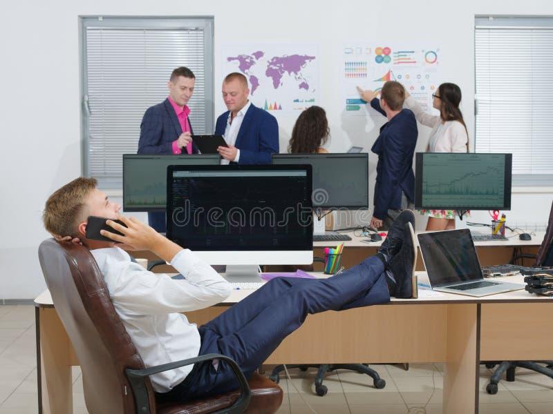 Stilig ung grabb i dräkt som talar på mobiltelefonen som i regeringsställning sitter med fot på skrivbordet fotografering för bildbyråer