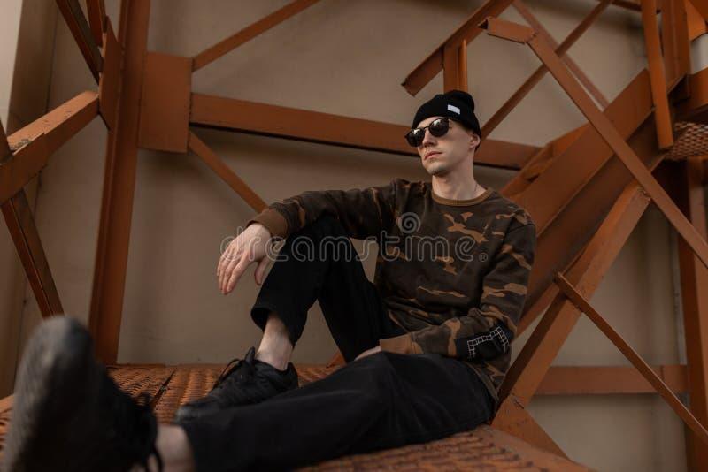 Stilig ung hipsterman i stilfull militär skjorta i svart hatt för tappning i mörk solglasögon i jeans i lädergymnastikskor royaltyfria bilder
