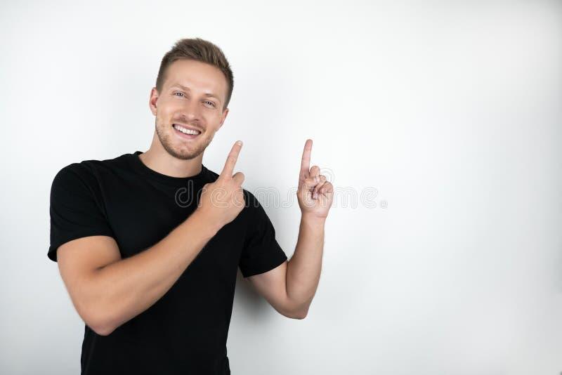 Stilig ung le man som bär den svarta t-skjortan som pekar med hans fingrar upp isolerad vit bakgrund royaltyfri fotografi