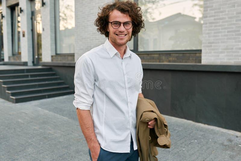 Stilig ung lycklig affärsman med exponeringsglas som utomhus ler och poserar Manlig student i höstgata Smart grabb i den vita skj fotografering för bildbyråer