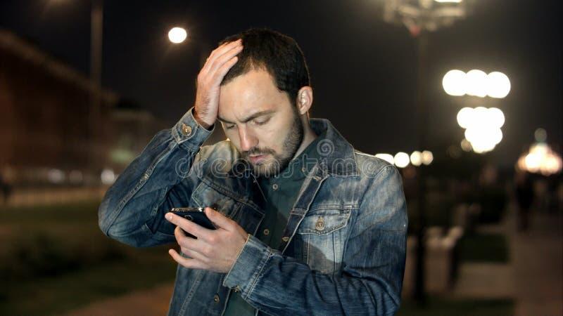 Stilig ung man, chockat som är förvånad med textmeddelandet arkivbild
