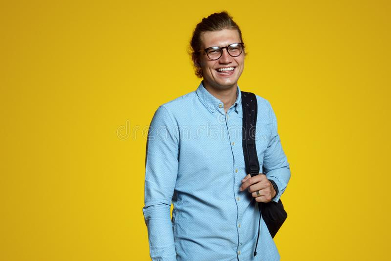Stilig ung man i blå skjorta och glasögon som rymmer ryggsäcken och ler på kameran på den gula bakgrunden royaltyfri foto