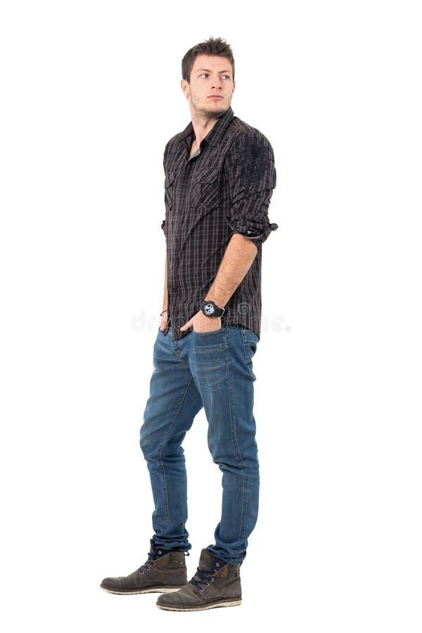 Stilig ung man i den mörka gråaktiga plädskjortan som tillbaka ser över skuldra royaltyfri fotografi