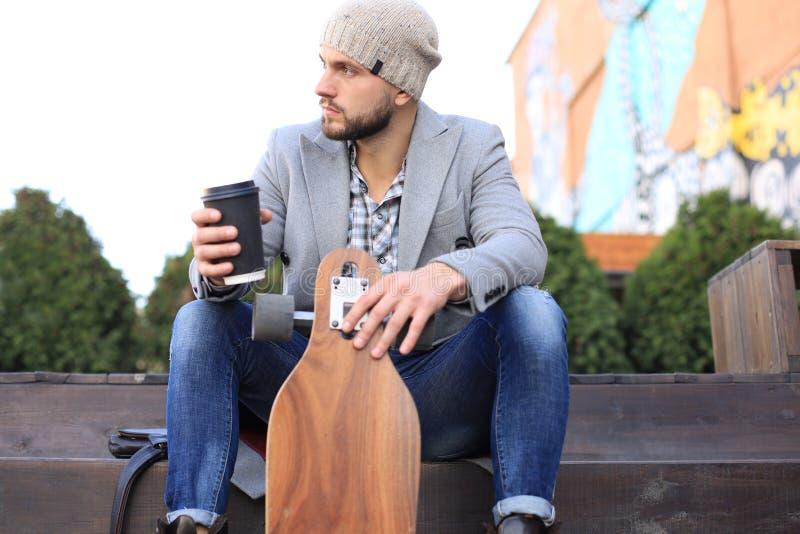 Stilig ung man i det gråa laget och hatten, vila som sitter med longboard som dricker kaffe Stads- skateboarding begrepp royaltyfria foton
