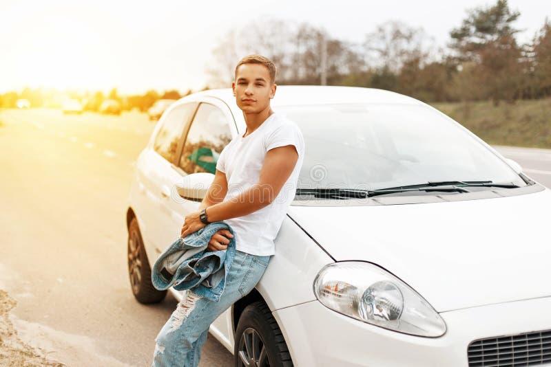 Stilig ung man i en vit ärmlös tröja nära bilen på solnedgången fotografering för bildbyråer