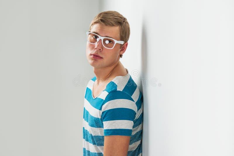 Stilig ung man i exponeringsglas som poserar att luta på väggen royaltyfri fotografi