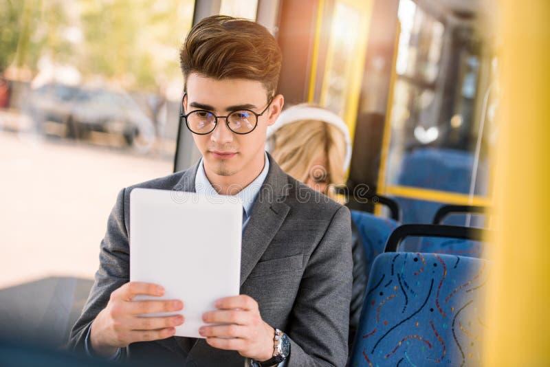 stilig ung man i glasögon genom att använda den digitala minnestavlan royaltyfri fotografi