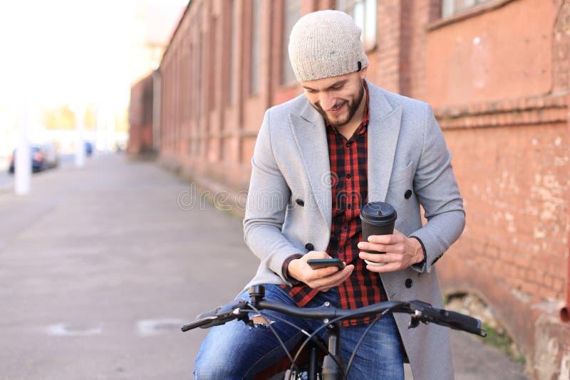 Stilig ung man i grått lag och hatt och se telefonen, medan skjuta hans cykel bredvid honom arkivbild