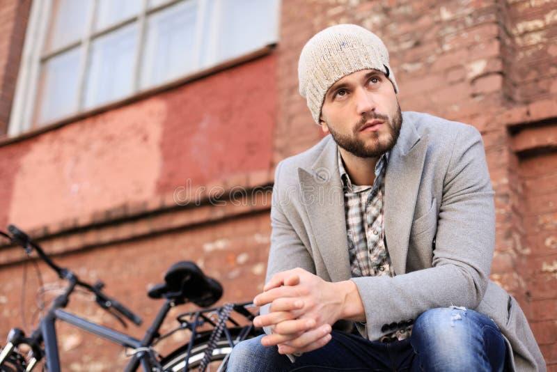 Stilig ung man i grått lag och hatten som sitter på en avkopplad bänk och utomhus tänker nära hans cykel arkivbild