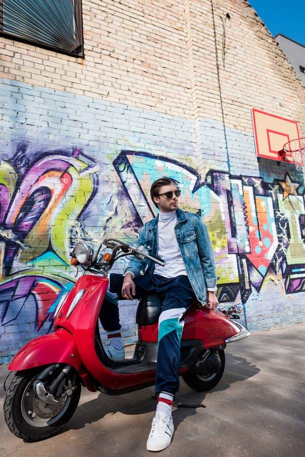 stilig ung man i stilfull kläder på den röda sparkcykeln för tappning framme av tegelstenväggen royaltyfri foto
