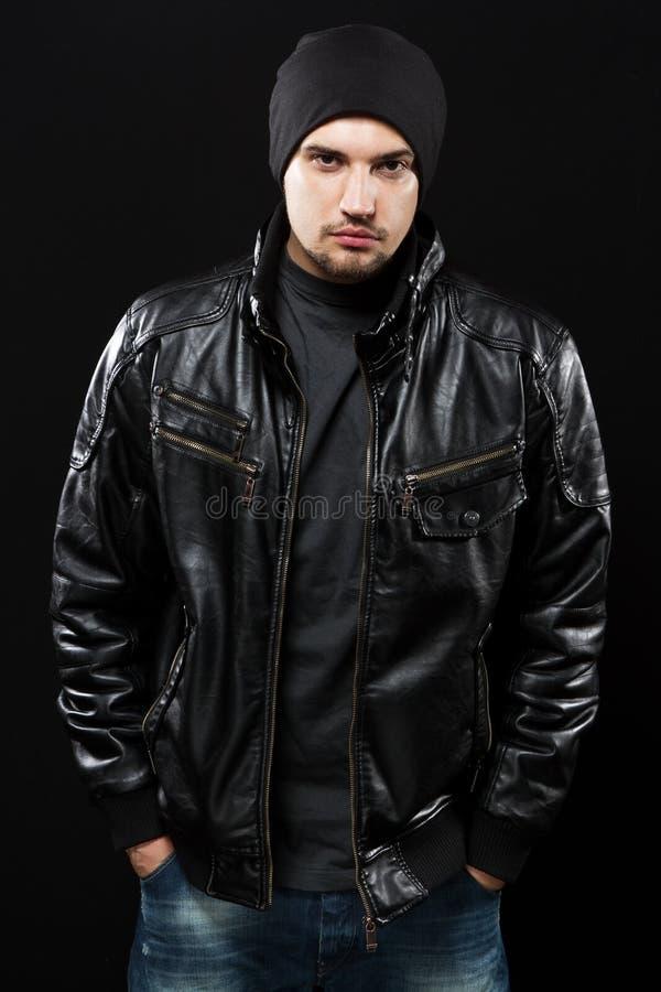 Stilig ung man i svart läderomslag fotografering för bildbyråer