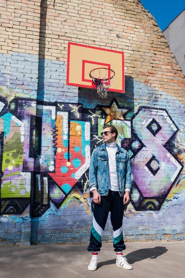 stilig ung man i tappning som framme beklär av tegelstenväggen med grafitti royaltyfria bilder