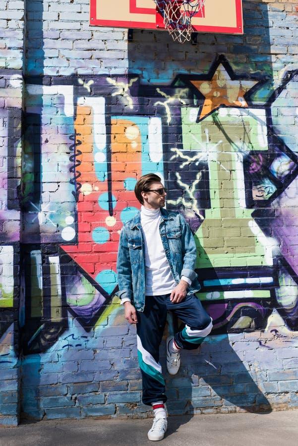 stilig ung man i tappningklädbenägenhet på tegelstenväggen royaltyfri foto