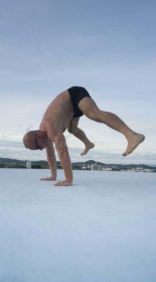 Stilig ung man med den nakna torson som gör bromsdansförehavanden på ett tak arkivbilder