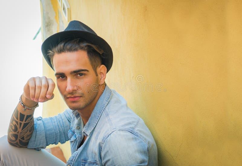 Stilig ung man med den svarta hatten fotografering för bildbyråer