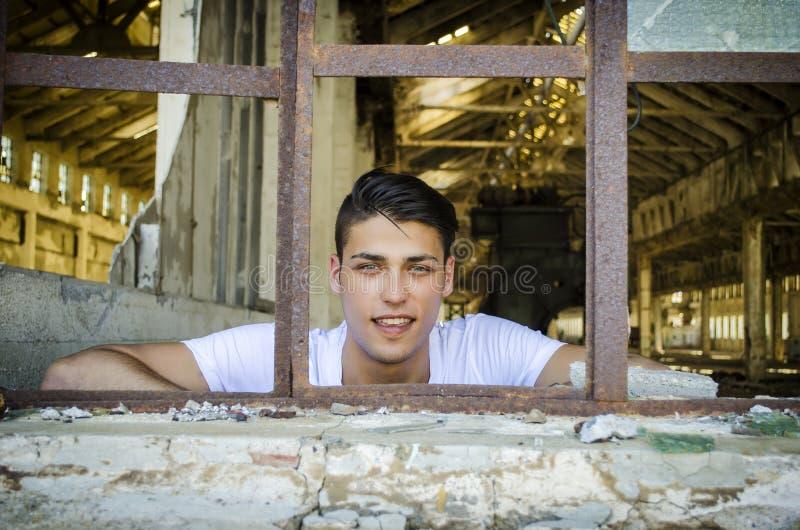 Stilig ung man med lyckligt uttryck i rostigt arkivfoto