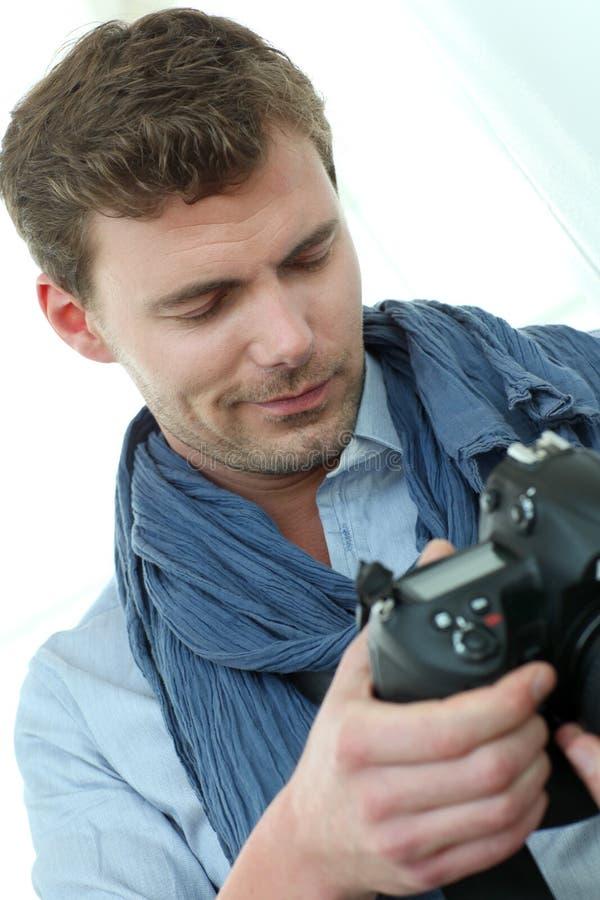 Stilig ung man med reflexkameran arkivbilder