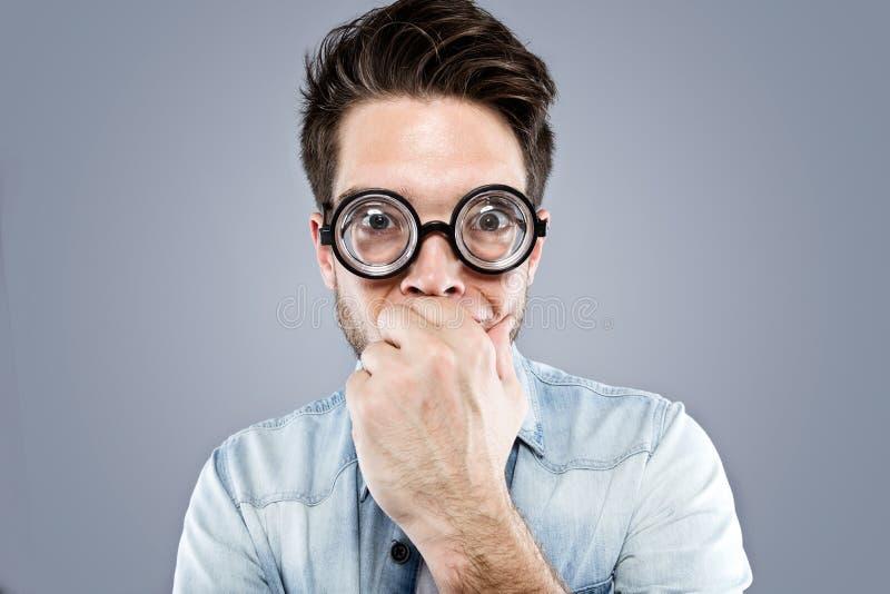 Stilig ung man med roliga exponeringsglas som skojar och gör den roliga framsidan över grå bakgrund fotografering för bildbyråer
