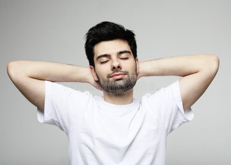 Stilig ung man med stängda ögon i smarta tillfälliga kläder som poserar över grå bakgrund arkivfoton
