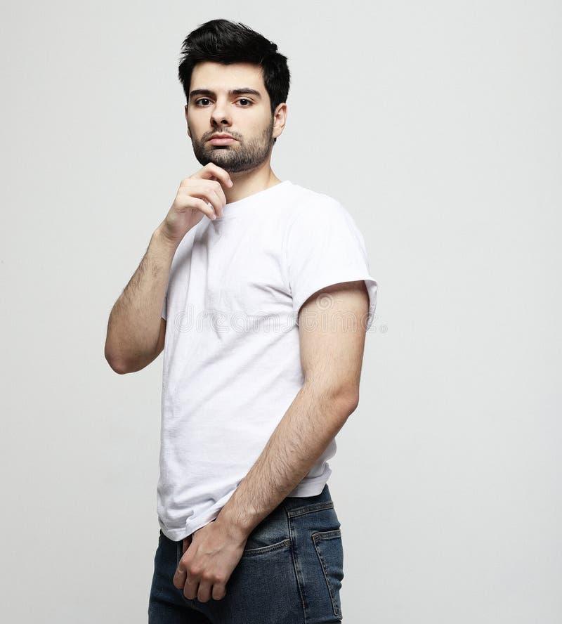 Stilig ung man, modemodell, i smarta tillfälliga kläder som ser kameran, över grå bakgrund royaltyfri bild