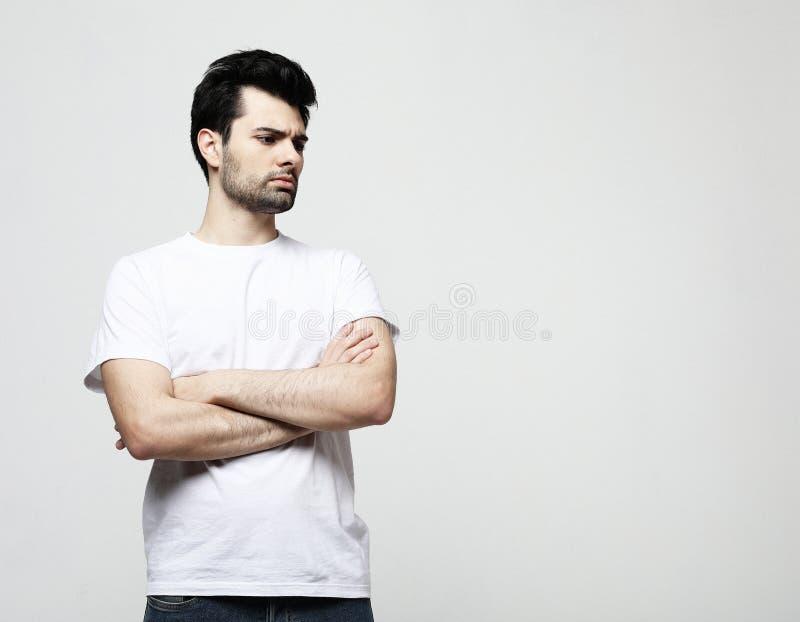 Stilig ung man, modemodell, i smarta tillfälliga kläder som ser kameran, över grå bakgrund royaltyfri fotografi