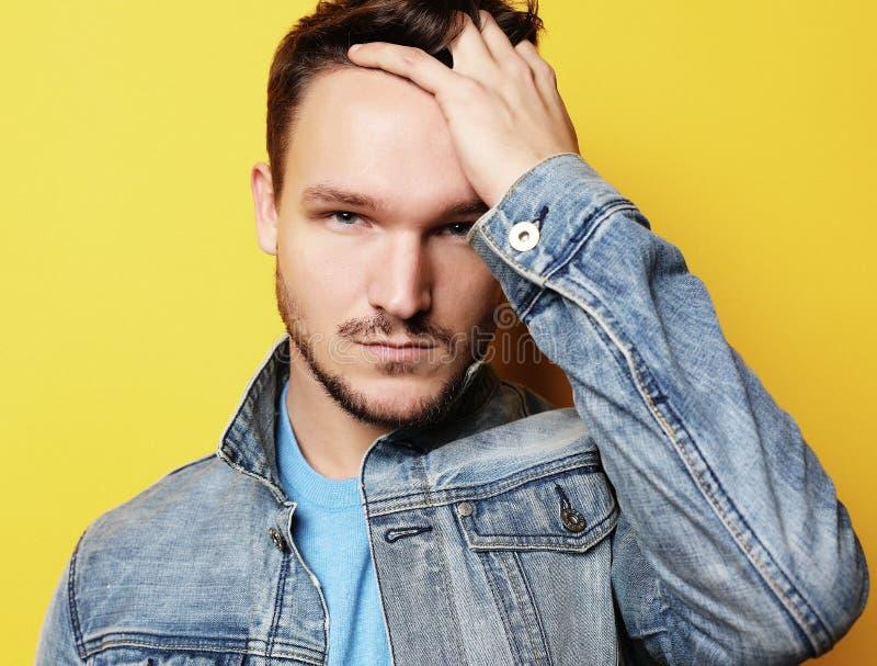 Stilig ung man, modemodell Posera över den gula väggen Livsstil och modebegrepp royaltyfri bild