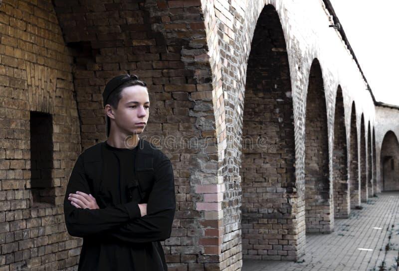 Stilig ung man nära en tegelstenvägg royaltyfria bilder