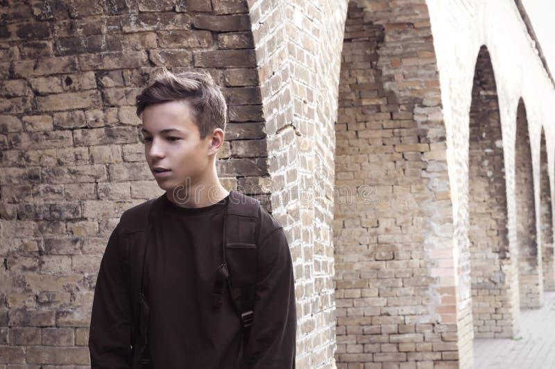 Stilig ung man nära en tegelstenvägg arkivfoto