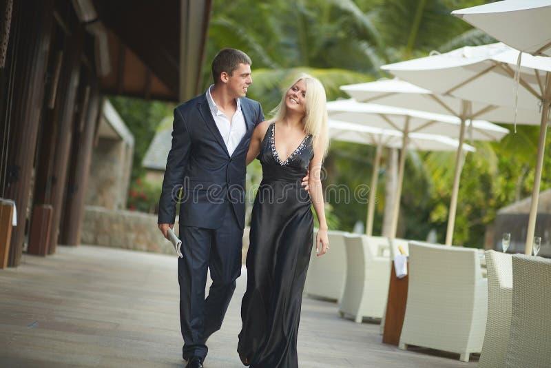 Stilig ung man och älskvärd kvinna som går utanför restaurangnolla royaltyfria foton