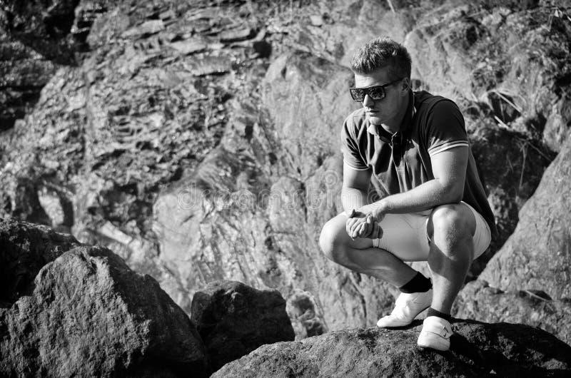 Stilig ung man på stenen som ner ser fotografering för bildbyråer