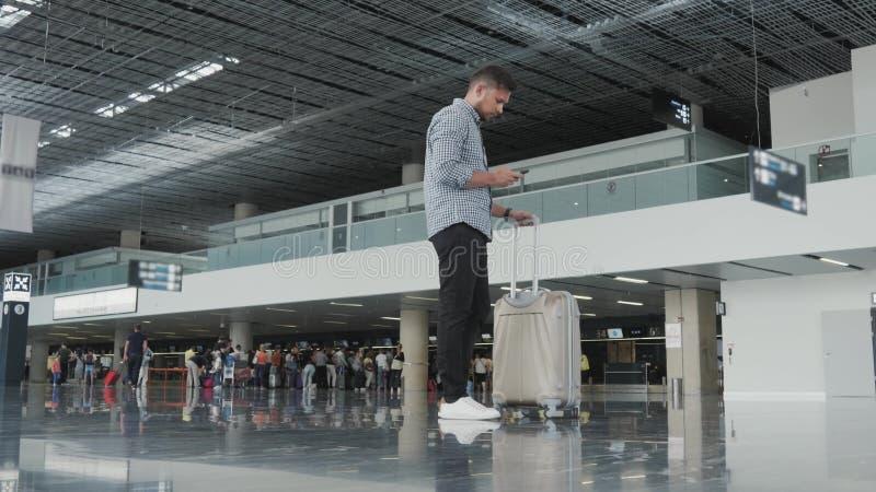 Stilig ung man som använder Smartphone och arbete på flygplatsen, medan vänta hans kö för registrering som reser arkivbild
