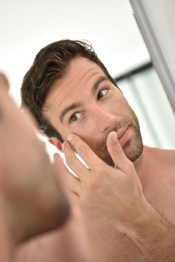Stilig ung man som applicerar ansiktsbehandlingkräm arkivfoto