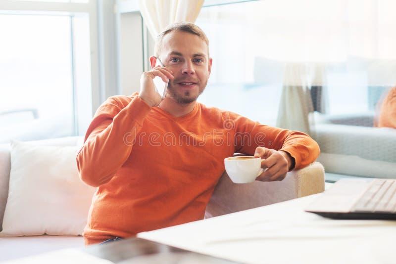 Stilig ung man som arbetar med anteckningsboken och att tala på telefonen, le som ser kameran, medan tycka om kaffe i kafé royaltyfri bild