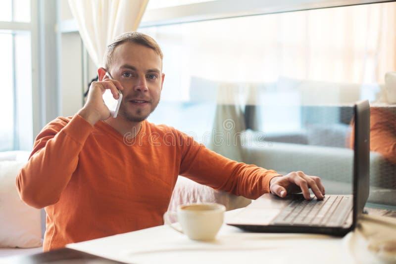 Stilig ung man som arbetar med anteckningsboken och att tala på telefonen som ser kameran, medan tycka om kaffe i kafé arkivfoton