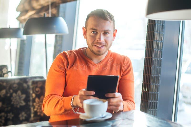 Stilig ung man som arbetar med minnestavlan som ser kameran, medan tycka om kaffe i kafé arkivbild