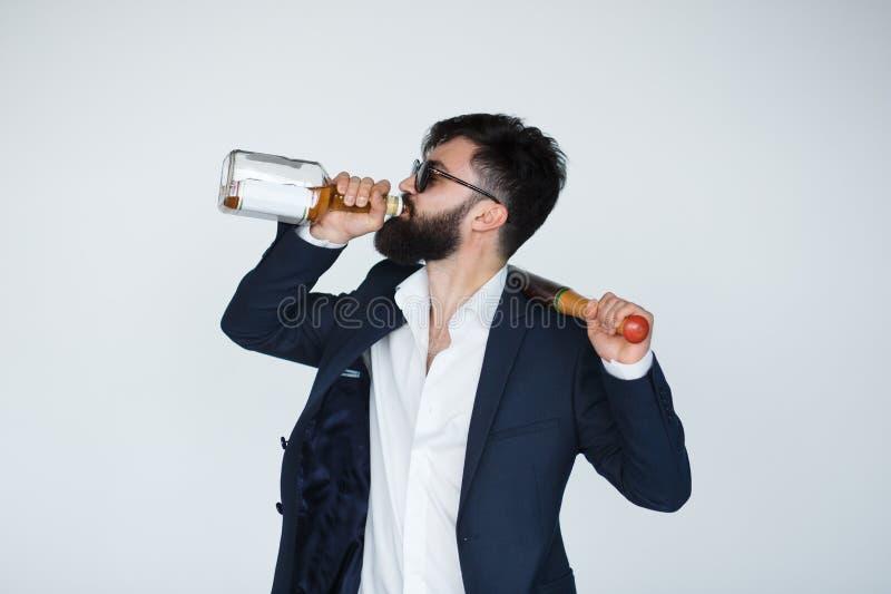 Stilig ung man som dricker från whiskyflaskan royaltyfri bild