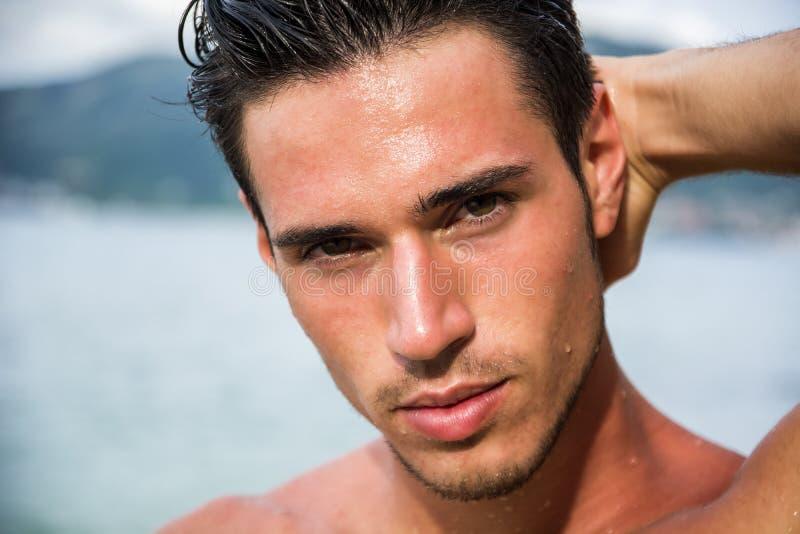 Stilig ung man som får ut ur vatten med vått hår arkivfoton