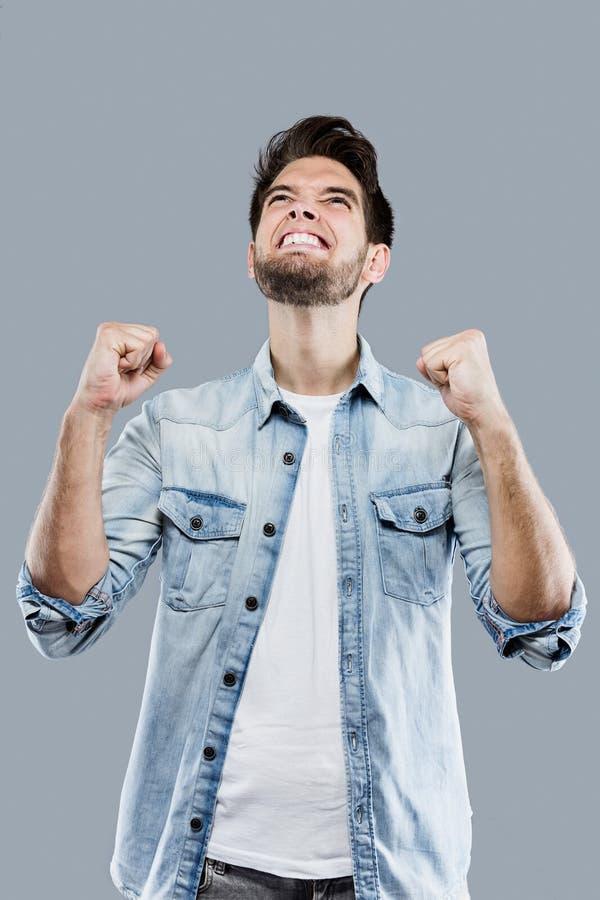 Stilig ung man som firar något över grå bakgrund arkivfoto