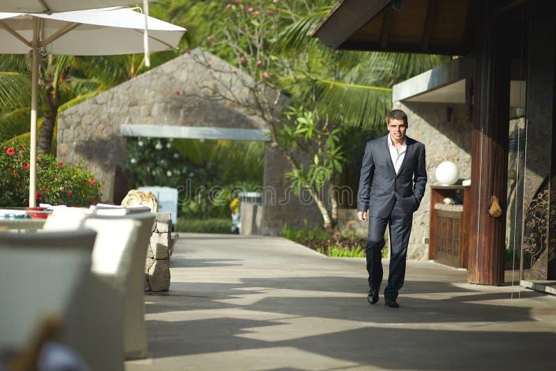 Stilig ung man som går utanför restaurang över terrass royaltyfria foton