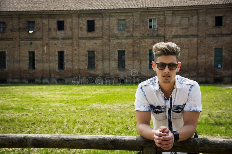 Stilig ung man som lutar utomhus på staketet royaltyfri bild