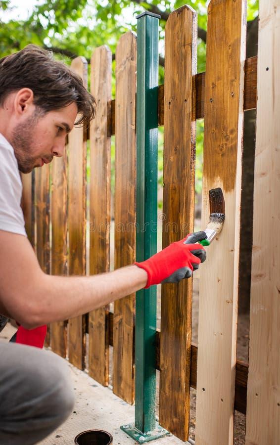 Stilig ung man som målar träyttersida med en borste royaltyfri bild