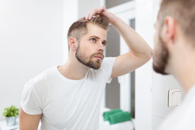 Stilig ung man som oroas om hairloss royaltyfri fotografi