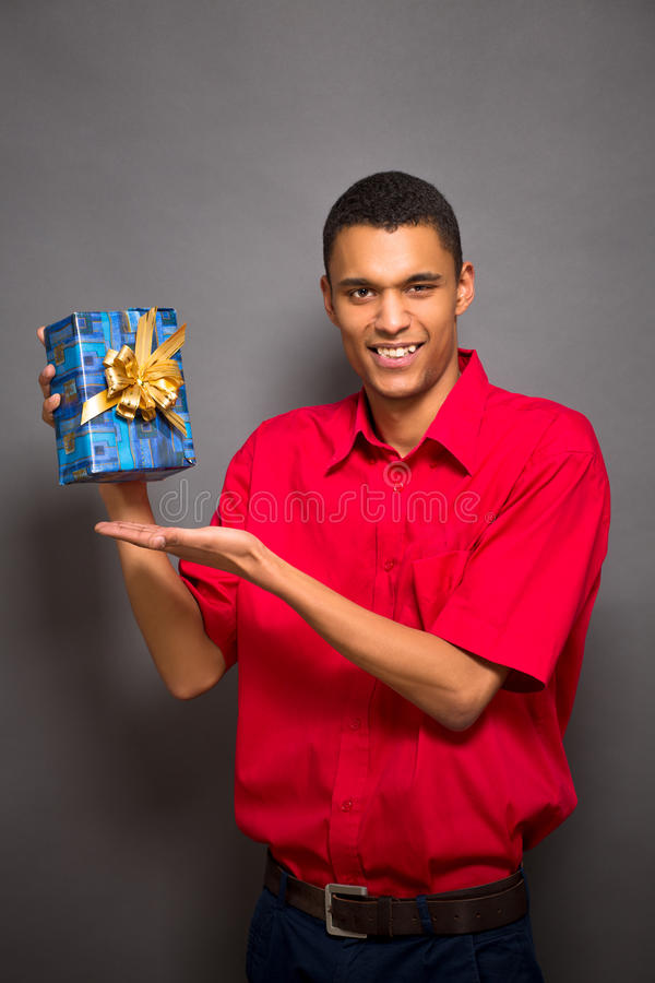 Stilig ung man som poserar med en gåva i studio royaltyfria bilder